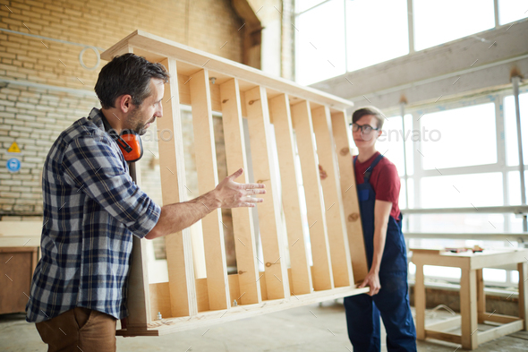 Workmen carrying wooden bed frame - Stock Photo - Images