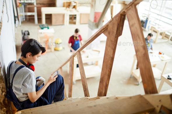 Lady carpenter having short break in workshop - Stock Photo - Images