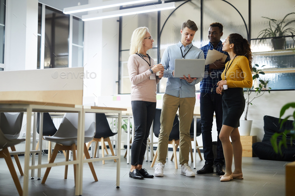 Colleagues analyzing online data in coworking space - Stock Photo - Images