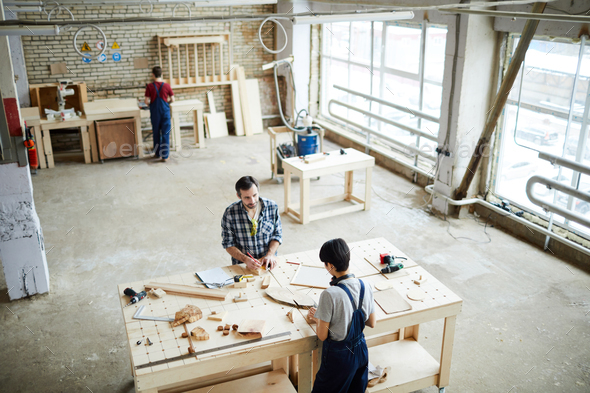 Carpentry workers making wooden frames in workshop - Stock Photo - Images