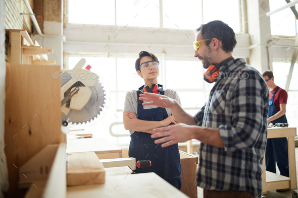 Carpenter giving advice to lady how to use circular saw - Stock Photo - Images