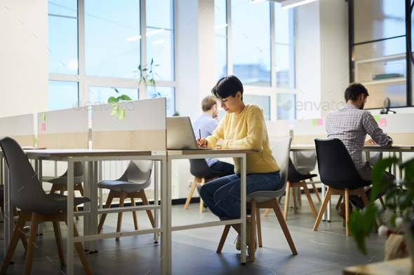 Student girl working on project in coworking space - Stock Photo - Images