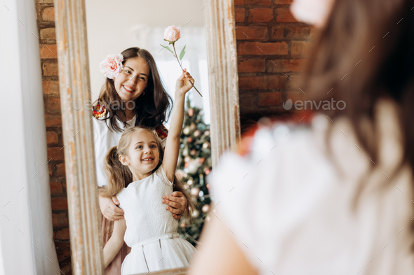 Young mother and her charming little daughter stand in front of the mirror in the room with New Year - Stock Photo - Images