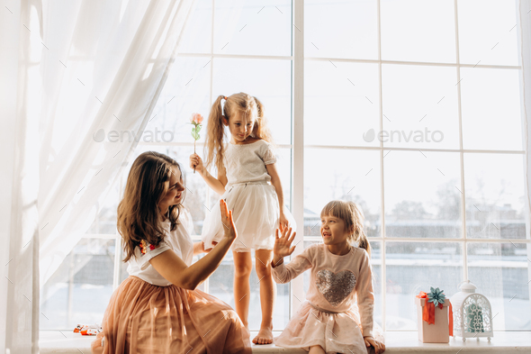 Two little sisters dressed in the beautiful dresses and there young mother sit on the windowsill - Stock Photo - Images