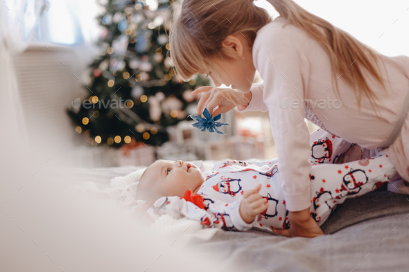 Little girl dressed in pajama is looking at her tiny brother lying on the bed in the cozy room with - Stock Photo - Images