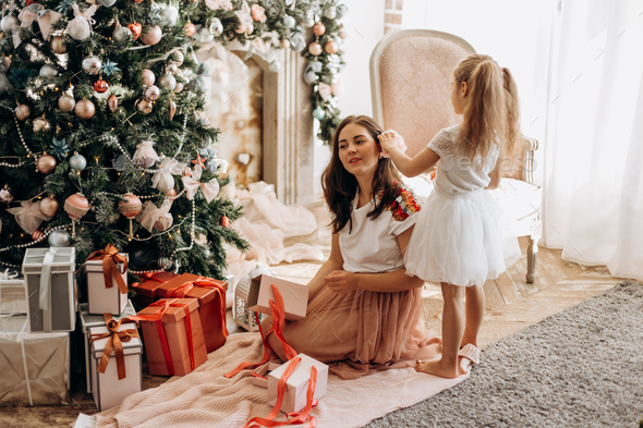 Happy young mother and her little daughter in nice dress sit near the New Year's tree and open - Stock Photo - Images