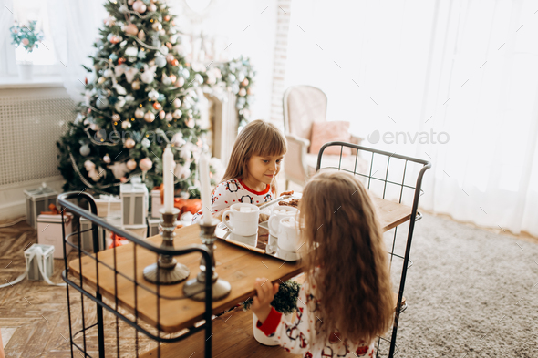 Two charming little girls sit at the table and are going to drink cocoa with Marshmallows and - Stock Photo - Images