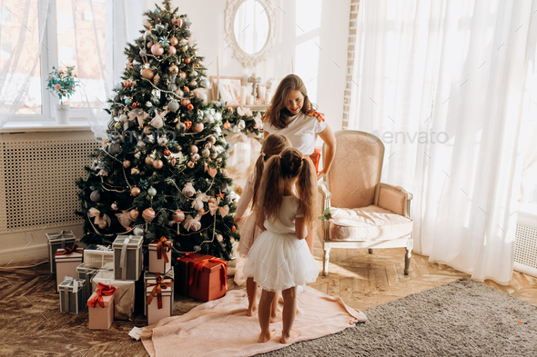 Young mother and her two charming daughter in nice dresses stand - Stock Photo - Images