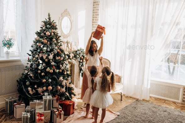 Happy young mother and her two charming daughter in nice dresses - Stock Photo - Images
