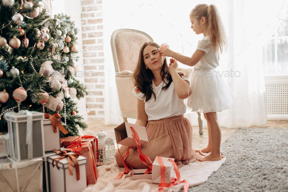 Happy young mother and her little daughter in nice dress sit ne - Stock Photo - Images
