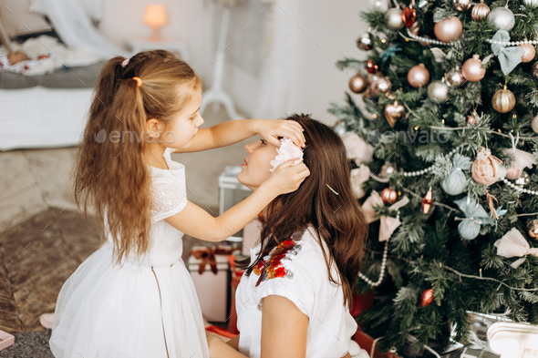 Charming little daughter in nice dress put a flower in mothers hair near the New Year's tree - Stock Photo - Images