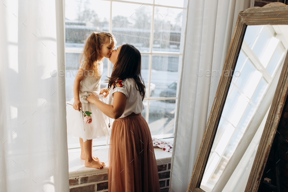 Young mother kisses her little daughter standing on the windowsill next to the mirror in the full of - Stock Photo - Images