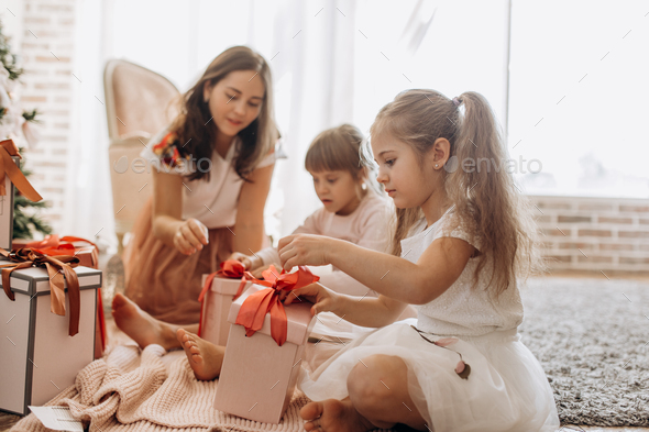 Happy young mother and her two charming daughters in nice dresses sit on the carpet and open New - Stock Photo - Images