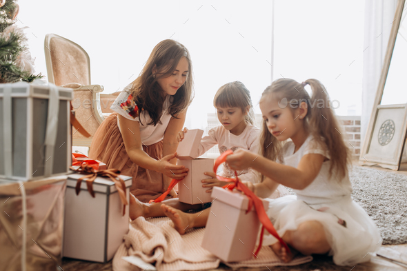 Happy young mother and her two charming daughters in nice dresse - Stock Photo - Images