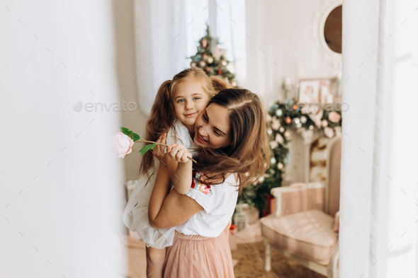 Young mother holds on her hands her little daughter in the cozy room with the New Year's tree - Stock Photo - Images
