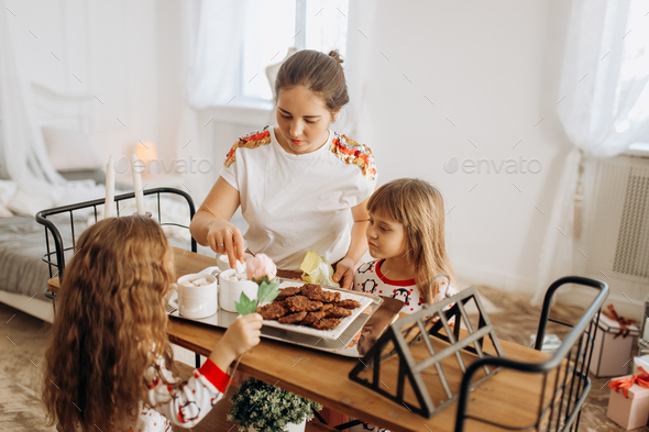 Young beautiful mother and her two charming little daughters sit - Stock Photo - Images