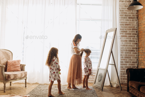 Young mother combing her little daughter's hair standing in front of the mirror and her second - Stock Photo - Images