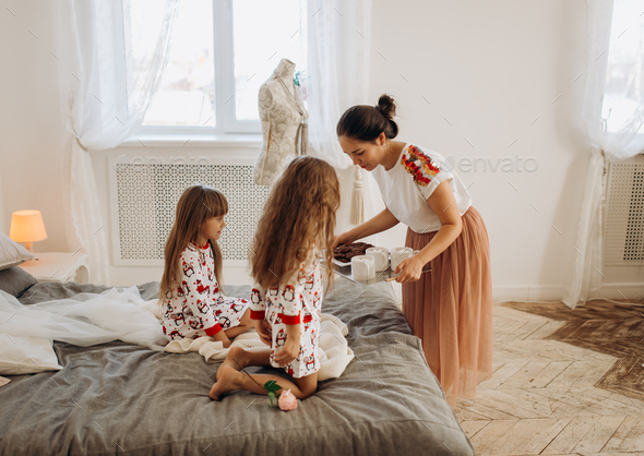 Young beautiful mother is bringing cocoa with Marshmallows and cookies to her daughters sitting on - Stock Photo - Images