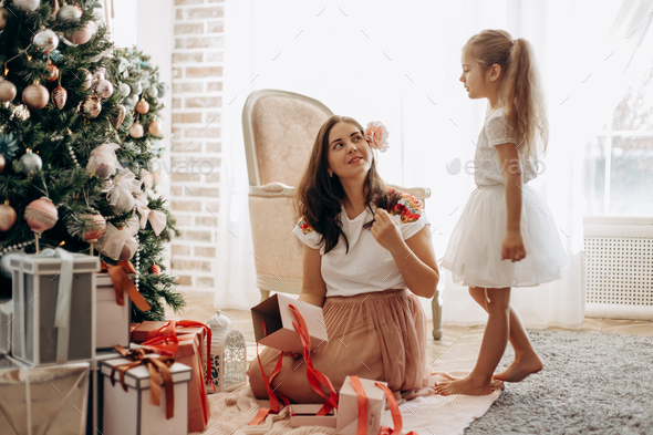 Happy young mother with flower in her hair and her little daughter in nice dress sit near the New - Stock Photo - Images