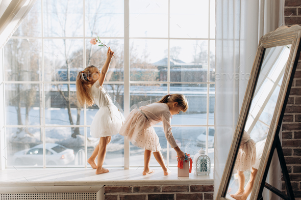 Two little sisters dressed in the beautiful dresses stand on the windowsill next to the mirror the - Stock Photo - Images