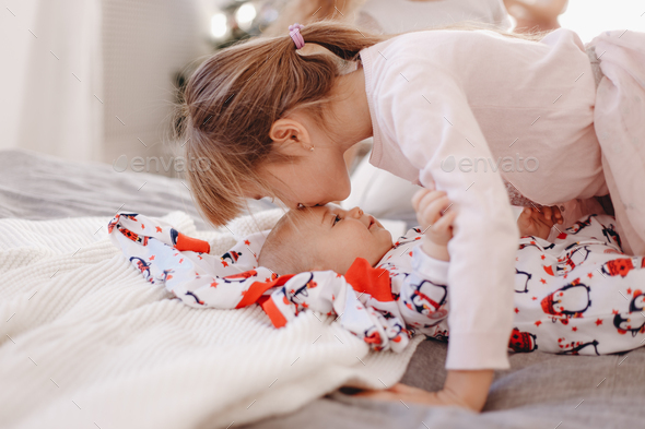 Little girl dressed in pajama kisses her tiny brother lying on the bed - Stock Photo - Images