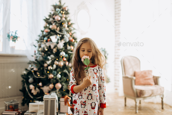 Charming little girl dressed in pajama holds a flower in the full of light cozy room with the New - Stock Photo - Images