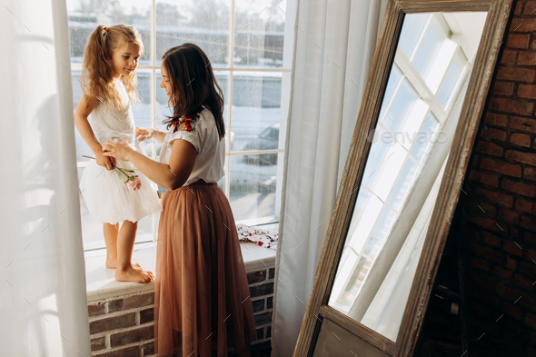 Young mother holds her little daughter standing on the windowsill next to the mirror in the full of - Stock Photo - Images