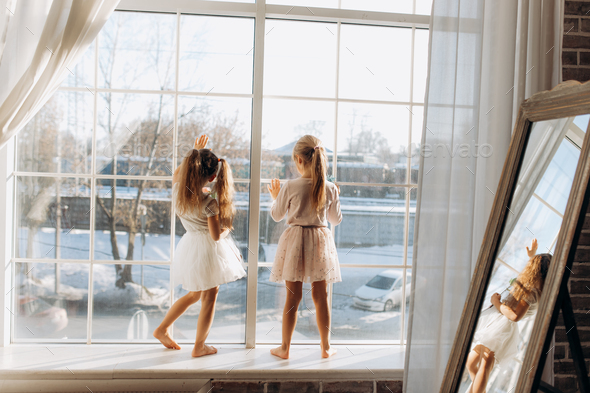 Two little sisters dressed in the beautiful dresses stand on the windowsill next to the mirror - Stock Photo - Images