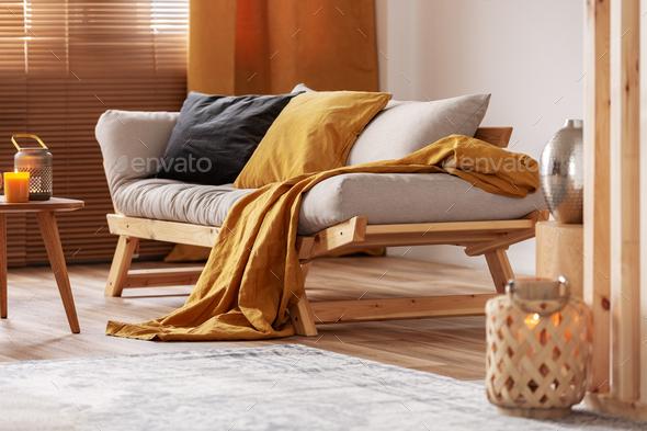 Closeup of comfortable Scandinavian sofa with futon and black and orange pillows - Stock Photo - Images