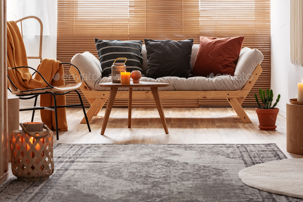 Vintage rug on wooden floor of contemporary living room interior with natural design - Stock Photo - Images