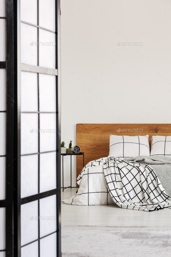 Elegant bedroom with white wall and chequered bedding - Stock Photo - Images