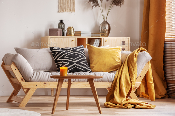 Orange candle on wooden coffee table in cozy living room interior - Stock Photo - Images