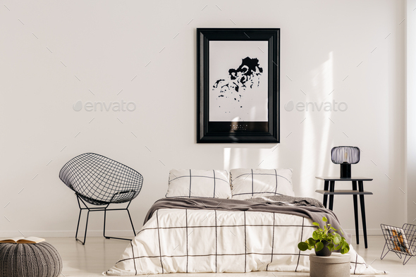 Fancy industrial armchair next to comfortable bed in bright interior - Stock Photo - Images