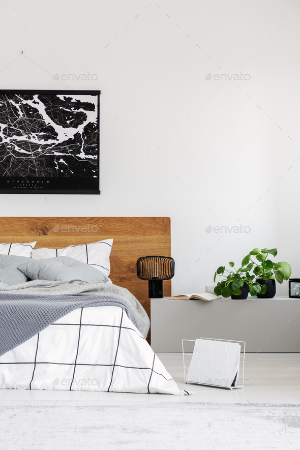 Copy space on white wall with black map in modern bedroom with king size bed with wooden headboard - Stock Photo - Images
