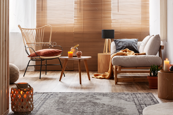 Stylish natural living room with raw wooden furniture and orange accents - Stock Photo - Images