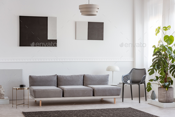 Trendy living room interior with white wall, painting and grey settee - Stock Photo - Images