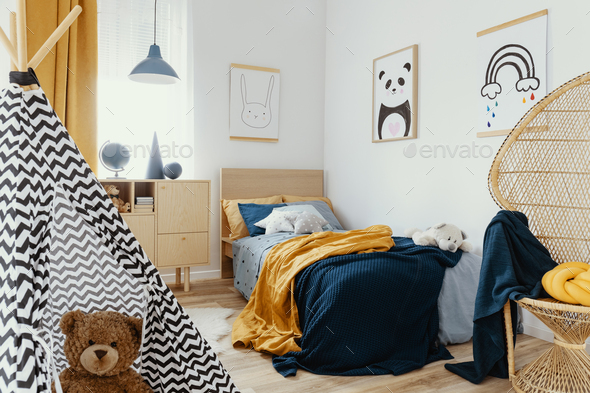 Stylish wooden commode in bright bedroom interior with poster on the wall - Stock Photo - Images