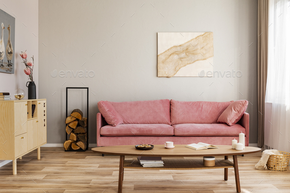 Pastel abstract painting on beige wall behind velvet pink settee in simple living room - Stock Photo - Images