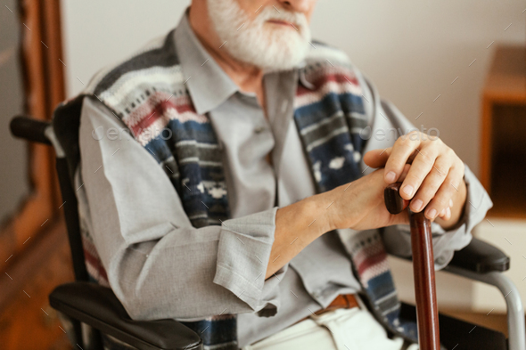 Alone elderly man sitting on the wheelchair and holding a walking stick - Stock Photo - Images