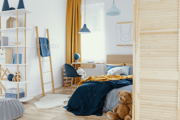 Messy kid's bedroom with toys and wooden furniture real photo - Stock Photo - Images