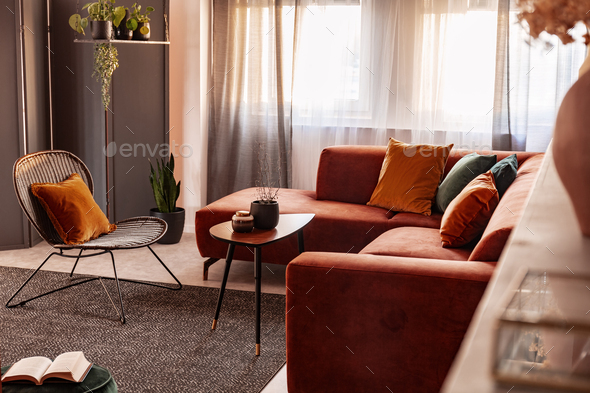 Small coffee table in front of comfortable corner sofa in autumn colored living room interior - Stock Photo - Images