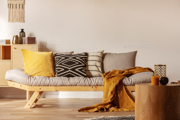 Copy space on empty white wall of fashionable living room interior with yellow and orange accents - Stock Photo - Images