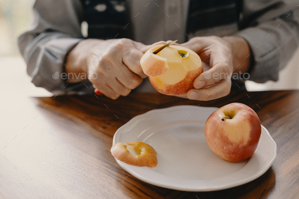 Senior caucasian man peeling an apple with a knife sitting at the wooden table - Stock Photo - Images