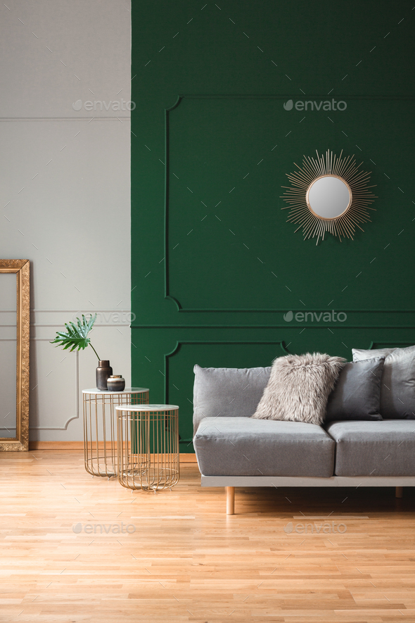 Sun shape mirror on empty green wall in stylish living room interior - Stock Photo - Images