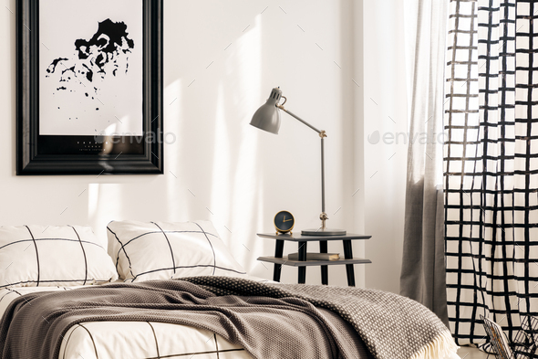 Industrial lamp on nightstand table next to king size bed in white bedroom interior - Stock Photo - Images