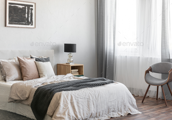 Cozy pillows on comfortable big king size bed in bright bedroom interior in elegant apartment - Stock Photo - Images