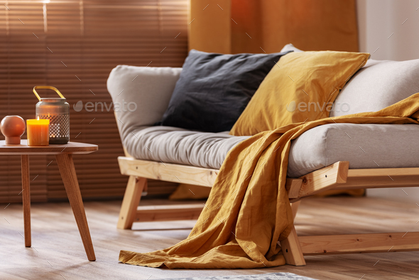 Closeup of comfortable Scandinavian sofa with futon and black and orange pillows - Stock Photo - Images