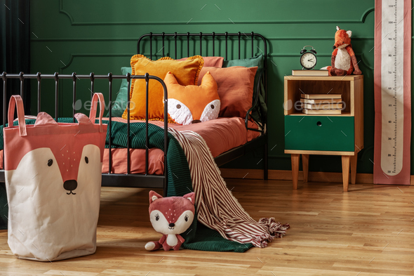 Fox theme in cute bedroom interior with green wall and orange bedding - Stock Photo - Images