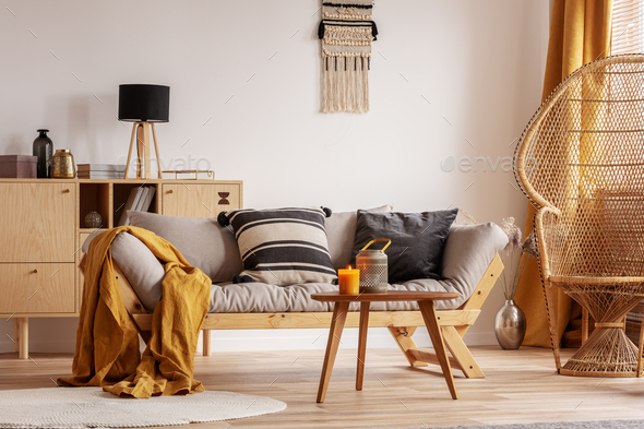 Stunning wicker peacock chair next to modern scandinavian settee with pillows - Stock Photo - Images