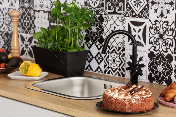 Cake, Herbs and fruits on kitchen counter in bright kitchen interior with trendy tiles on the wall - Stock Photo - Images